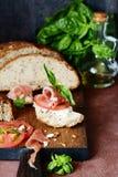 Bruschetta con jamon secco, formaggio cremoso, i pomodori ed il basilico fresco Tapas con Jamon affumicato Prosciutto di Parma di immagine stock