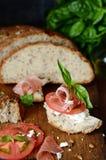 Bruschetta con jamon secco, formaggio cremoso, i pomodori ed il basilico fresco Tapas con Jamon affumicato Prosciutto di Parma di fotografia stock libera da diritti