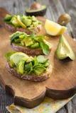 Bruschetta con l'avocado, la rucola, il limone ed i pinoli Fotografia Stock