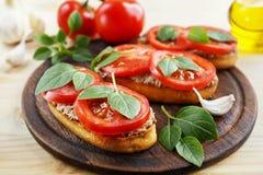 Bruschetta con la coronilla, los tomates y la albahaca Fotografía de archivo