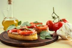 Bruschetta con la coronilla, los tomates y la albahaca Imagen de archivo libre de regalías