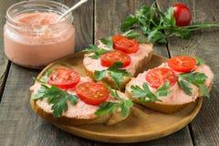 Bruschetta con la mantequilla de color salmón, caviar del capelín, tomates de cereza a fotografía de archivo
