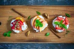 Bruschetta con le pesche, le prugne, le fragole e la ricotta Fotografie Stock Libere da Diritti