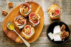 Bruschetta con los higos, la miel, el queso de cabra y las nueces Imagen de archivo libre de regalías