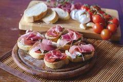 Bruschetta con los tomates de cereza, prosciutto, ajo, aceite de oliva Fotografía de archivo libre de regalías