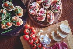 Bruschetta con los tomates de cereza, prosciutto, ajo, aceite de oliva Fotos de archivo