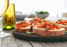 Bruschetta con los tomates, el queso de cabra y la albahaca imágenes de archivo libres de regalías