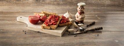 Bruschetta con los tomates en el fondo de madera foto de archivo