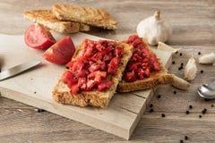 Bruschetta con los tomates en fondo de madera rústico imagen de archivo