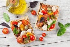 Bruschetta con los tomates, la mozzarella y la albahaca Imagen de archivo libre de regalías