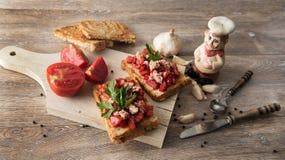 Bruschetta con los tomates y el atún en el fondo de madera fotografía de archivo libre de regalías