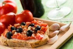 Bruschetta con los tomates y las aceitunas negras foto de archivo libre de regalías