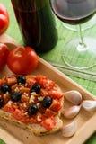 Bruschetta con los tomates y las aceitunas negras imagen de archivo libre de regalías