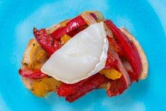 Bruschetta con pimientas y queso del ` s de la cabra en una placa de la turquesa Fotos de archivo