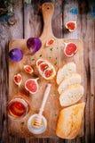 Bruschetta con queso de cabra, los higos frescos, la miel y el tomillo Imagenes de archivo