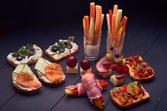 Bruschetta con queso de los salmones y del pepino y del tomate, de la albahaca y de la mozzarella en el tablero de madera Italian foto de archivo libre de regalías