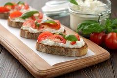 Bruschetta con queso Feta del queso, los tomates y la albahaca en cuttin de madera suben Imágenes de archivo libres de regalías