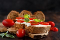 Bruschetta with cream cheese, cherry tomatoes and basil. On a wooden table Royalty Free Stock Images