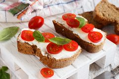 Bruschetta with cream cheese, cherry tomatoes and basil. On a wooden table Royalty Free Stock Photography