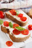 Bruschetta with cream cheese, cherry tomatoes and basil Royalty Free Stock Photos