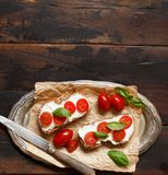 Bruschetta with cream cheese, cherry tomatoes and basil. On a wooden table Royalty Free Stock Image