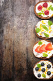 Bruschetta with cream cheese, fresh berries, chia seeds and honey. Royalty Free Stock Photography