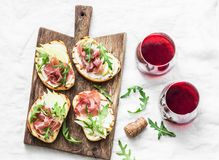 Bruschetta with cream cheese, pear, prosciutto, arugula on wooden chopping board and red wine  on light background, top view Royalty Free Stock Image