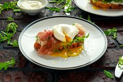 Bruschetta with cream cheese, wilde rucola, parma ham and poached egg served on white plate. Stock Photo