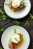 Bruschetta with cream cheese, wilde rucola, parma ham and poached egg served on white plate. Stock Photography