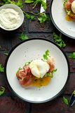 Bruschetta with cream cheese, wilde rucola, parma ham and poached egg served on white plate. Stock Images