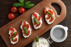 Bruschetta crujiente hecho en casa con queso Feta, el tomate y la albahaca en tabla de cortar de madera Imagen de archivo