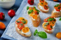 Bruschetta de la albahaca del tomate del Ricotta con los tomates y la albahaca frescos le Fotografía de archivo libre de regalías