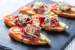 Bruschetta del aperitivo con el prosciutto, tomate, calabacín en el pan del ciabatta en el cierre de piedra del fondo de la pizar Fotos de archivo libres de regalías