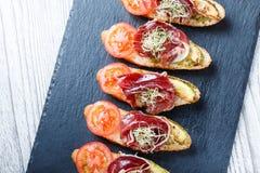 Bruschetta del aperitivo con el prosciutto, tomate, calabacín en el pan del ciabatta en el cierre de piedra del fondo de la pizar Imagen de archivo