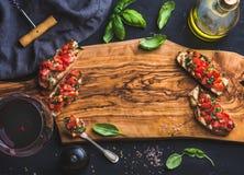 Bruschetta del basilico e del pomodoro con vetro di vino rosso, olio d'oliva, sale, erbe fresche sul bordo di legno sopra fondo n immagini stock libere da diritti