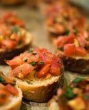 Bruschetta del pomodoro: miscela del basilico del pomodoro sopra un pane Immagini Stock