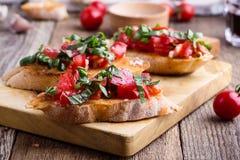 Bruschetta del tomate y de la albahaca con pan de ajo tostado Imagen de archivo libre de regalías