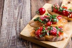 Bruschetta del tomate y de la albahaca con pan de ajo tostado Fotografía de archivo libre de regalías