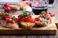 Bruschetta del tomate y de la albahaca con pan de ajo tostado Fotos de archivo libres de regalías