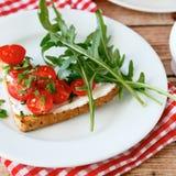 Bruschetta delicioso con las rebanadas de tomates en una placa blanca Imagen de archivo libre de regalías