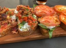 Bruschetta with delicious variety of toppings served on a board Stock Photos