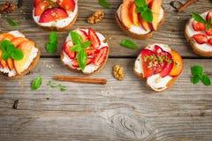 Bruschetta della prima colazione di estate con le prugne, fragole, pesche immagini stock