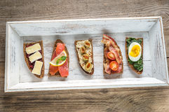 Bruschetta with different toppings on the wooden tray Stock Images