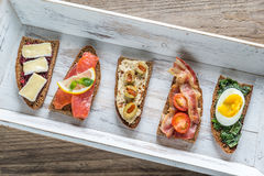 Bruschetta with different toppings on the wooden tray Stock Image