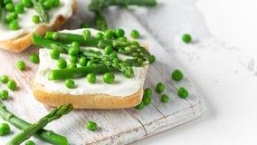 Bruschetta do aperitivo, brinde com aspargo, ervilhas e queijo macio cremoso na placa branca Alimento saudável imagens de stock
