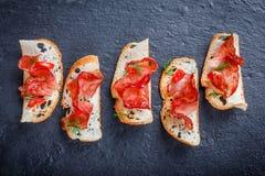Bruschetta do aperitivo com o prosciutto espasmódico no pão acima finamente cortado do ciabatta no fim de pedra do fundo da ardós Imagens de Stock Royalty Free