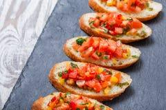 Bruschetta do aperitivo com os vegetais desbastados no pão do ciabatta no fim de pedra do fundo da ardósia acima Foto de Stock