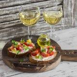 Bruschetta do tomate e do queijo e dois vidros do vinho branco em uma placa de corte de madeira rústica Foto de Stock