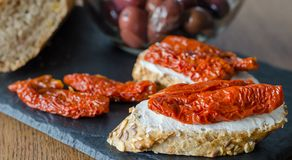 Bruschetta with dried tomatoes and soft cheese with boil of olives. Traditional Italian cuisine sandwich. Antipasti royalty free stock photography
