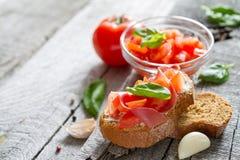 Bruschetta en ingrediënten op rustieke houten achtergrond Stock Fotografie